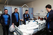 AFC Wimbledon defender Will Nightingale (5), AFC Wimbledon defender Rod McDonald (26), AFC Wimbledon midfielder Anthony Hartigan (8), AFC Wimbledon attacker Egli Kaja (21), delivering Christmas presents to the children on behalf of AFC Wimbledon, at St George's Hospital, Tooting, United Kingdom on 13 December 2018.