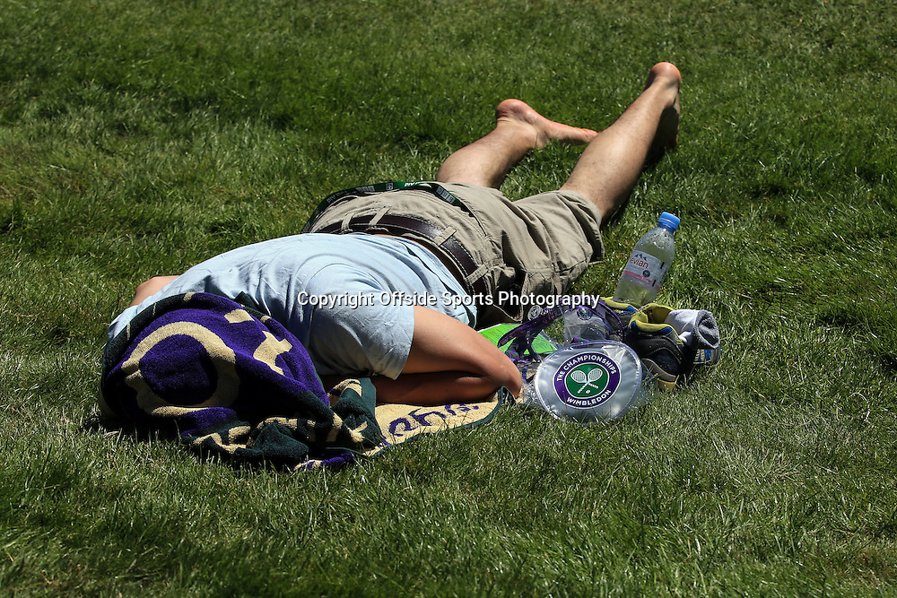 30 June 2015 - Wimbledon (Day 2) - A man lays  on Murray mound, head wrapped in a Wimbledon towel as he shields himself from the high temperartures - Photo: Marc Atkins / Offside.