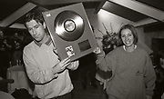 Party guests with 'Bummed' gold disc, Factory Records party, Manchester, 1989