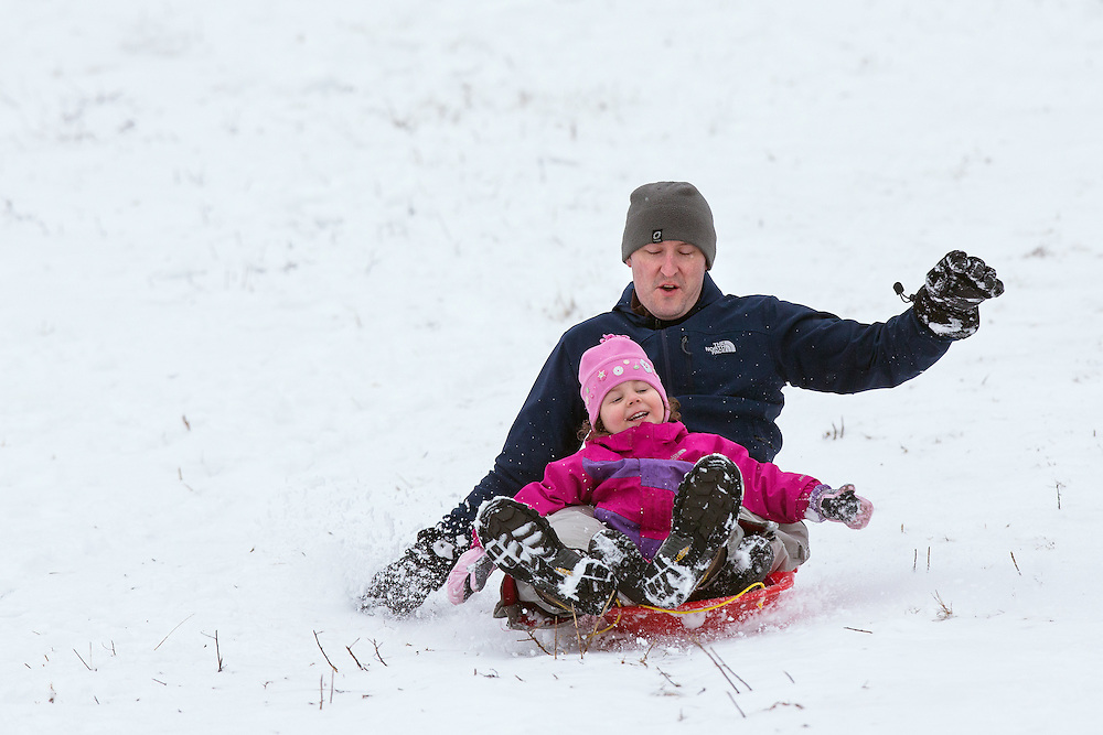 GABE GREEN/Press<br /> <br /> Gabby DeSomma, 3, sleds down Cherry Hill with her dad Josh before school Wednesday.