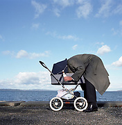 Man sticking head into baby pram by seafront, side view