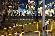 Local community passes a hoarding showing aspiration and consumerism of nearby Westfield City shopping complex, Stratford. Situated on the fringe of the 2012 Olympic park, Westfield hosted its first day to thousands of shoppers eager to see Europe's largest urban shopping centre. The £1.45bn complex houses more than 300 shops, 70 restaurants, a 14-screen cinema, three hotels, a bowling alley and the UK's largest casino. It will provide the main access to the Olympic park for the 2012 Games and a central 'street' will give 75% of Olympic visitors access to the main stadium so retail space and so far 95% of the centre has been let. It is claimed that up to 8,500 permanent jobs will be created by the retail sector.