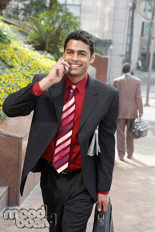 Business man using mobile phone on city street