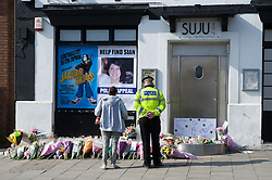 © under license to London News Pictures.  25/03/201. A police officer and member of the public look at flowers outside the SUJU nightclub in the Wiltshire town of Swindon, where personal assistant Sian O'Callaghan, was last seen alive. Her murdered body was found yesterday by police. Picture credit should read: London News Pictures