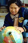 Cambodian woman age 35 locating her country on the globe.  St Paul  Minnesota USA
