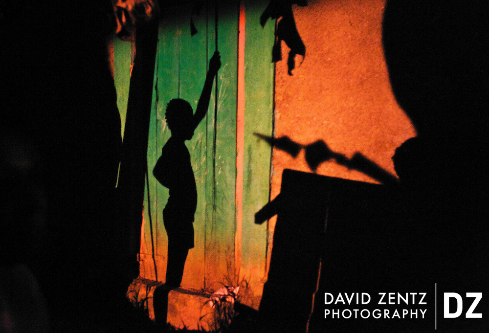 A young girl's shadow is cast on the side of a house in the village of Ville de Bonheur, Haiti.