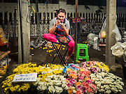 30 JUNE 2016 - BANGKOK, THAILAND: A woman selling flowers from a sidewalk stall at Pak Khlong Talat. Sidewalk vendors around Pak Khlong Talat, Bangkok's famous flower market, face eviction if they reopen on July 1. As a part of the military government sponsored initiative to clean up Bangkok, city officials have been trying to shut down the sidewalk vendors around the flower market. The vendors were supposed to be gone by the end of March, but city officials relented at the last minute with a compromise allowing vendors to stay until June 30. When vendors dismantled their booths after business on June 30, they weren't sure if they will be allowed to reopen July 1. Some vendors have moved to new locations approved by the government but many have not because they can't afford the higher rents in the new locations.     PHOTO BY JACK KURTZ