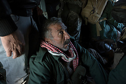 © Licensed to London News Pictures. 11/12/2014. Sinjar Mountains, Iraq. A Yazidi fighter sits on the floor of an Iraqi Air Force Mi-17 Hip helicopter after clambering through a door during a mission to resupply trapped Yazidi refugees on Mount Sinjar.<br /> <br /> Although a well publicised exodus of Yazidi refugees took place from Mount Sinjar in August 2014 many still remain on top of the 75 km long ridge-line, with estimates varying from 2000-8000 people, after a corridor kept open by Syrian-Kurdish YPG fighters collapsed during an Islamic State offensive. The mountain is now surrounded on all sides with winter closing in, the only chance of escape or supply being by Iraqi Air Force helicopters. Photo credit: Matt Cetti-Roberts/LNP