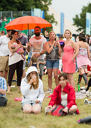 © Licensed to London News Pictures. 20/07/2014. Southwold, UK.   Festival goers shelter from the rain at  Latitude Festival 2014 Day 3.  This weekend has seen hot sunny weather mixed with thunderstorms.    Latitude is an British annual music festival.  Photo credit : Richard Isaac/LNP
