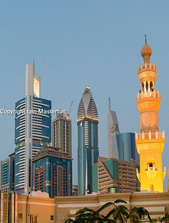 Mosque minarets and skyline of skyscrapers in Dubai United Arab Emirates UAE
