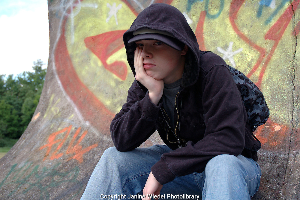 Young boy hanging around the streets dressed in hoodie looking threatening and bored.