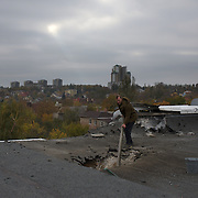 DONETSK, UKRAINE - OCTOBER 19, 2014: A volunteer worker checks the damaged to the roof of the gymnastic pavilion of School 61 in central Donetsk, hours after it was hit by shell presumably shot by the Ukrainian National Guard troops fighting for the control of the city's airport area. CREDIT: Paulo Nunes dos Santos