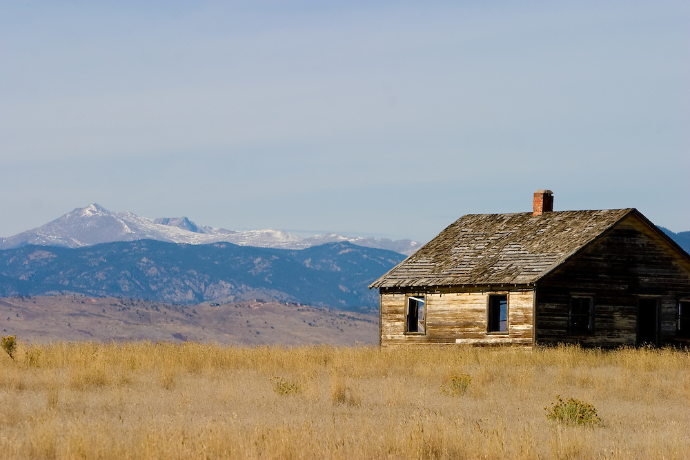 An old abandoned farm house stands against a backdrop of the Rocky Mountains in the far distance.