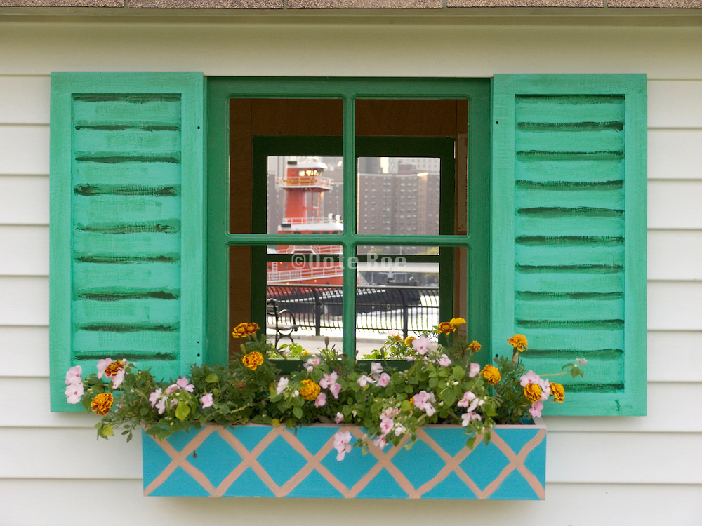idyllic windows with flower box looking out to our world tugboat on the East River NYC