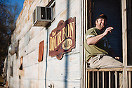 Owner Mark Azlin smokes on the front porch of the Bourbon Mall, a restaurant near Leland, Mississippi.