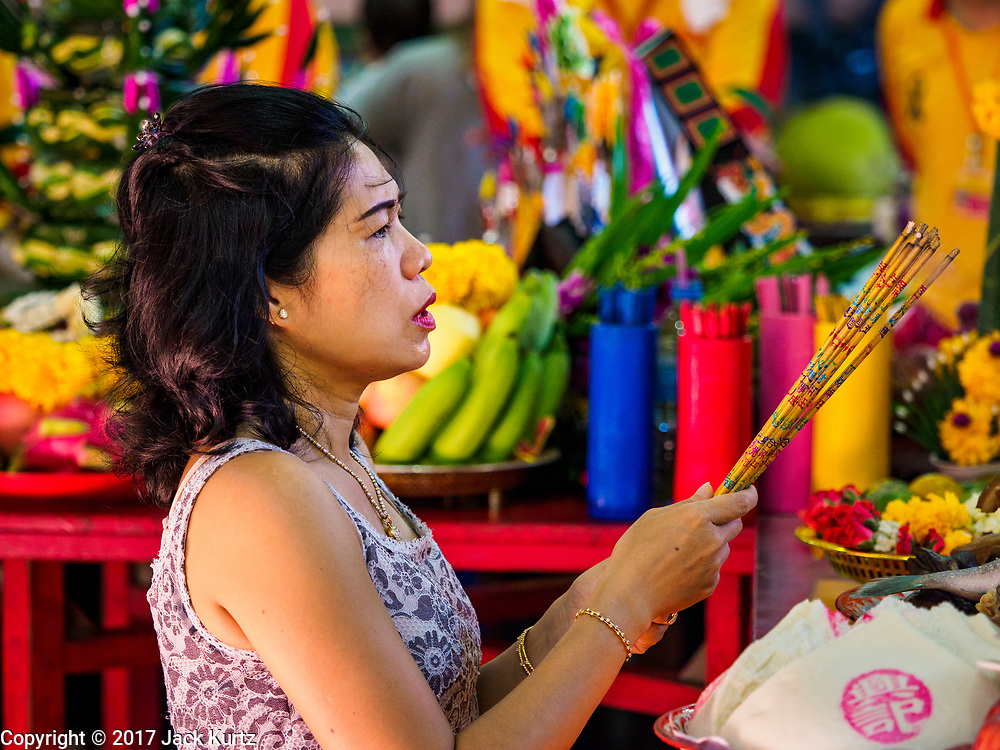 "02 JUNE 2017 - SAMUT SAKHON, THAILAND:  A woman prays before the City Pillar Shrine parade in Samut Sakhon. The Chaopho Lak Mueang Procession (City Pillar Shrine Procession) is a religious festival that takes place in June in front of city hall in Samut Sakhon. The ""Chaopho Lak Mueang"" is  placed on a fishing boat and taken across the Tha Chin River from Talat Maha Chai to Tha Chalom in the area of Wat Suwannaram and then paraded through the community before returning to the temple in Samut Sakhon. Samut Sakhon is always known by its historic name of Mahachai.     PHOTO BY JACK KURTZ"
