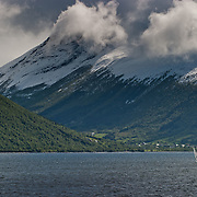 Three weeks aboard the Kong Harald. Hurtigruten, the Coastal Express. Landscape near Alesund and the Geirangerfjord. Snow on the mountains and clouds in the sky.
