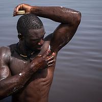 Un homme s'enduit le corps de beurre de karité pour proteger sa peau du sel.