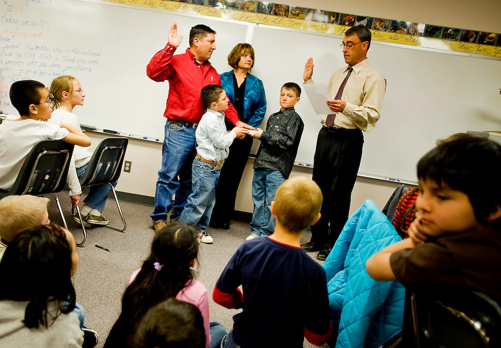 011209     Brian Leddy.State Senator George Munoz, his wife Sharmyn, and two sons Zane and Landon surround him while Judge Lious De Pauli reads him his oath at Red Rock Elementary school on Monday. Students from both Zanes fourth-grade class and Landon's second grade class attended the ceremony.