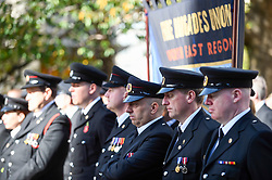 © Licensed to London News Pictures. 13/10/2018. LONDON, UK.  Members of the Fire Brigades Union (FBU) during a minute's silence in memory of fallen firefighters at the formal wreath-laying ceremony, one wreath for every fire service in the UK, at the National Firefighters' Memorial next to St Paul's Cathedral.  The ceremony was followed by commemorations of the centenary of the formation of the FBU by a formal procession across the Millennium Bridge and a service at Southwark Cathedral. The activities are the largest ever ceremonial event for firefighters killed in the line of duty.  Photo credit: Stephen Chung/LNP