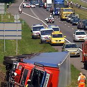 NLD/Blaricum/20050711 - Gekantelde vrachtwagen met gewonde chauffeur snelweg A27 ter hoogte Blaricum..file, chaos, verkeer, ambulance, brandweer, hulp, hulpverlening,