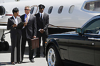Mid-adult businesswoman, senior businessman and chauffeur in front of private airplane.