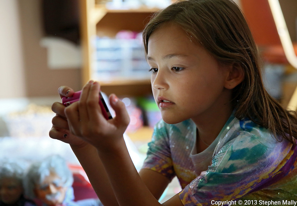 """Raegan Junge, 8, of Keystone looks at some pictures in her """"office"""" at her house in Keystone on Wednesday, July 17, 2013."""
