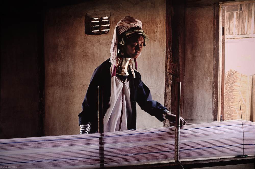 — A Padaung woman, of the Red Karen people, weaves a traditional garment on a hand loom. The Padaung women and young girls work for a Shan owner; they weave as well as pose for the tourists visiting Inle Lake. The Shan are the largest ethnic group in the region, also the richest from exploiting the smaller ethnic minorities, treating them like slaves.