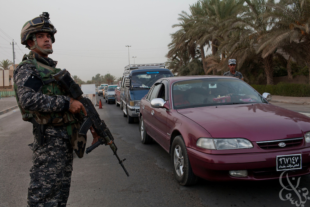 Iraqi Federal Policemen check cars at the entrance to the Amil neighborhod in Southwest Baghdad, Iraq August 23, 2010.  The number of Iraqi police and army checkpoints across the city has  dramatically increased as Iraqi forces try to gain the upper hand on security now that American combat forces have withdrawn. . .