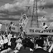 The activists had hid bamboo poles in nearby fields and when the had out run the police they managed to set up tripods across the road leading to the Coryton refinery, blocking any traffick coming through. Tall tripods with people on top make it very difficult for the police to clear with out risking causing injuries..The plastic footballs were for comfort and activists took turn during the day to sit in the tripods...Crude Oil Awakening is a coalition of climate change activist groups. On Saturday Oct 16 they shut the only entrance to Coryton oil refinery in Essex, UK with the aim of highlighting the issues of climate change and the burning of fossil fuels. The blockade meant that a great number of trucks with oil were not able to leave the refinary during the day of action.