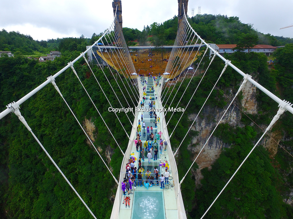 ZHANGJIAJIE, CHINA - JUNE 25:<br /> <br /> Aerial view of the glass-bottomed bridge receiving a safety test at Zhangjiajie Grand Canyon on June 25, 2016 in Zhangjiajie, Hunan Province of China. World\'s tallest and longest glass-bottomed bridge has been completed and took a global broadcast through television and internet medias to show its safety. More than thirty citizens and visitors thumped the bridge with hammer in the test event. <br /> &copy;Exclusivepix Media
