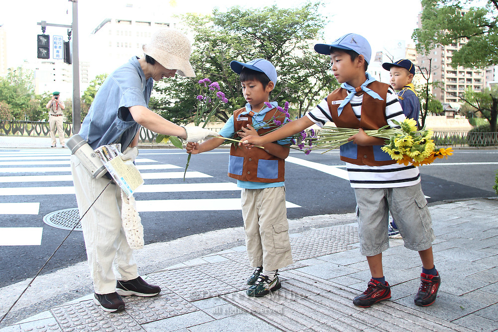 Aug. 06, 2010 ; Hiroshima, JPN - The Hiroshima and Asa District Boy Scouts passed out flowers and pamphlets to people as they arrived at the 2010 Hiroshima Peace Memorial Ceremony in Peace Park.