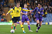 Oxford United defender defender (on loan from Columbus Crew SC) Chris Cadden (2) looks to release the ball  under pressure from Shrewsbury Town midfielder Luke Goss (22) during the EFL Sky Bet League 1 match between Oxford United and Shrewsbury Town at the Kassam Stadium, Oxford, England on 7 December 2019.