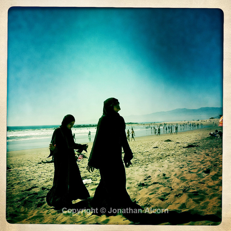 Two muslim women both wearing the traditional burqa walk on the sandat Venice Beach as a record of 92 degrees was set in downtown Los Angeles today, according to the National Weather Service breaking a 45 year old record. Two muslim women both wearing the traditional hijab and burqa walk on the sand