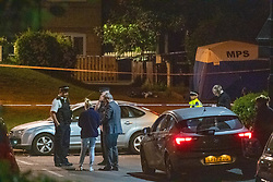 © Licensed to London News Pictures. 18/05/2020. London, UK. Police talking in front of a police forensic tent on Wiltshire Gardens. Police were called at 20:22BST to reports of shots fired in Wiltshire Gardens, N4. Metropolitan Police Service attended along with London Ambulance Service and found a man, believed to be aged in his 20s, suffering gunshot injuries. The man was pronounced dead at the scene. Photo credit: Peter Manning/LNP