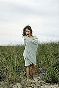 Girl wrapped in a beach towel walking through dune grass, Brewster, Cape Cod, MA