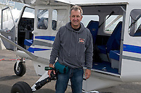 Photographer Mark Carwardine with plane used for aerial photography, Akureyri, Iceland