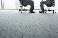 Low section of businessmen sitting on office chairs