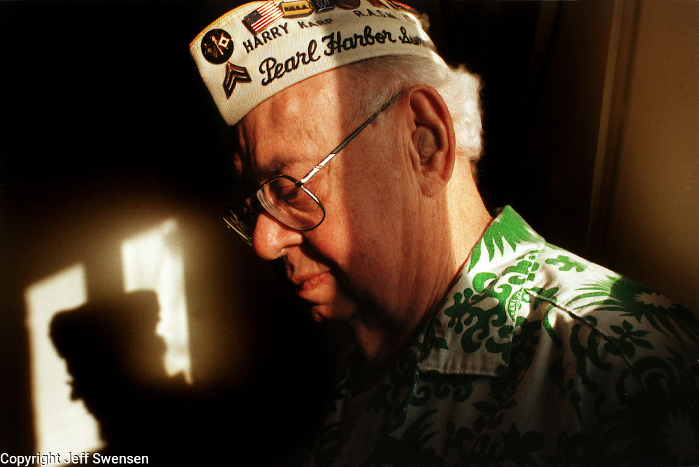 As the evening sun sets on the 49th eve of the anniversary Pearl Harbor invasion, survivor Harry Karp of New Kensington  bows his head in remembrance of his fallen comrades wearing his Hawaiian Pearl Harbor Survivors shirt.