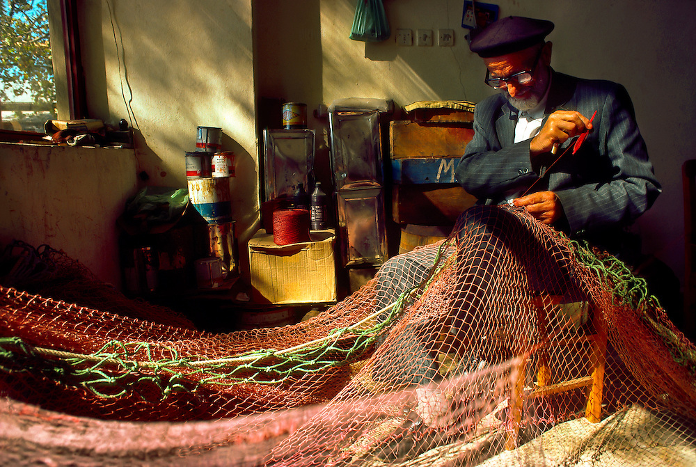 Turkish fisherman repairing fishing net, Anadolukavagi (on the Bosporus Straight, near the Black Sea), Turkey