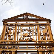 """Nederland Rotterdam 12 januari 2008 20080112 Foto: David Rozing ..Kunstwerk Delftsche Poort ( stadspoort ) een reconstructie in staal opgericht in 2005, ontworpen door de kunstenaar Cor Kraat naast Hofplein in het centrum van Rotterdam ...Piece of art """" Delftsche Poort """" Reconstruction of old city gate building in the centre of Rotterdam  ....?.De Delftsche Poort in Rotterdam was een stadspoort die in 1764 werd gebouwd naar een ontwerp van architect Pieter de Swart. Het was reeds de derde poort met die naam: de voorgaande twee waren wegens bouwvalligheid gesloopt. De eerste St. Joris- of Delftsche Poort werd in 1545 gebouwd..In de jaren '30 van de 20e eeuw stond de poort in de weg Men besloot de poort zo'n honderd meter te verplaatsen (afbreken stuitte op te veel weerstand). In 1939 begon men met de verplaatsing van het geheel. De onderbouw was in 1940 gereed, tijdens het bombardement werden zowel dit gedeelte als de opgeslagen beeldhouwwerken beschadigd. Een jaar later werd besloten dat """"naar het inzicht van de meerderheid van de geraadpleegde deskundigen de poort niet meer afgebouwd kon worden en moest zij geheel verdwijnen"""". Enkele sierwerken werden gered en opgenomen in de muren van de gebouwen op de hoek van het Stadhuisplein..Vijftig jaar later werd er op nagenoeg de oorspronkelijke plaats van de Delftsche poort aan het Pompenburg een reconstructie in staal opgericht, ontworpen door de kunstenaar Cor Kraat. Rond de poort zijn enkele restanten opgesteld van de gebeeldhouwde ornamenten die de oorspronkelijke poort sierden.....Foto: David Rozing"""