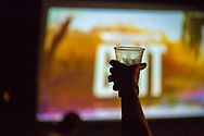 "Merrick, New York, USA. 11th June 2017.  At a Viewing Party for the premiere of ""American Grit"" Season 2, a woman guest cheers and holds up a plastic drink cup then silhouetted in front of large TV, in backyard of contestant Chris Edom. Edom family hosted neighborhood party during broadcast of that episode of the FOX network reality television series."