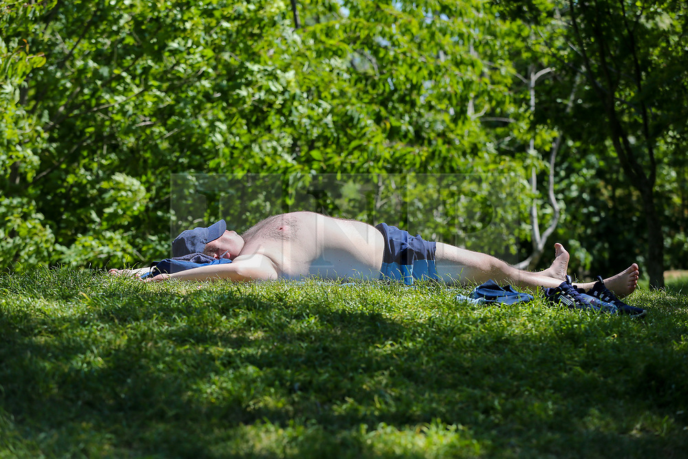 © Licensed to London News Pictures. 20/05/2020. London, UK. A man sunbathes in Markfield Park, Tottenham, north London on a warm and sunny day in London. The government has relaxed the rules on the COVID-19 lockdown, allowing people to spend more time outdoors whilst following social distancing guidelines. According to the Met Office, 27 degrees celsius is forecast for today.  Photo credit: Dinendra Haria/LNP