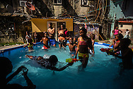 Children swim and enjoy a pool filled with water during a block party outside of the crumbling building where they live in Colón, Panama. Despite being the second largest city in Panama, Colón is one of the poorest in the region, and its residents suffer from a critical shortage of potable water and sewer connections. Much of the waste water in Colón flows freely into the streets, contaminating the ground and causing illness among children living in the area.  Panama is now one of the fastest growing countries in Latin America and there is a growing resentment and impatience that basic municipal services like water and waste removal are infrequent and unreliable.