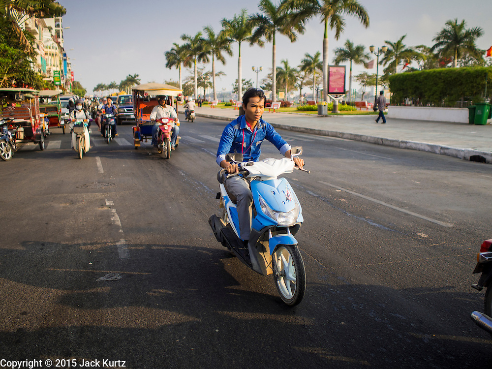 25 FEBRUARY 2015 - PHNOM PENH, CAMBODIA: A motorcycle in traffic on Sisowath Quay in Phnom Penh.    PHOTO BY JACK KURTZ