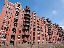 Historic red brick warehouse buildings beside canal in Speicherstadt district in Hamburg Germany