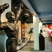 "A bronze statue titled ""Beating Gongs"" and sculpted by artist Mo Lo Kai in 1970. The museum was opened on July 17, 1956, two years after the victory over the French at Dien Bien Phu. It is also known as the Army Museum (the Vietnamese had little in the way of naval or air forces at the time) and is located in central Hanoi in the Ba Dinh District near the Lenin Monument in Lenin Park and not far from the Ho Chi Minh Mausoleum."