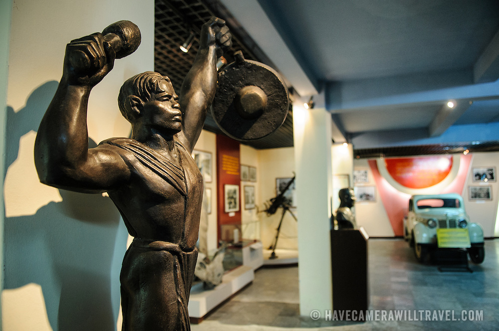 """A bronze statue titled """"Beating Gongs"""" and sculpted by artist Mo Lo Kai in 1970. The museum was opened on July 17, 1956, two years after the victory over the French at Dien Bien Phu. It is also known as the Army Museum (the Vietnamese had little in the way of naval or air forces at the time) and is located in central Hanoi in the Ba Dinh District near the Lenin Monument in Lenin Park and not far from the Ho Chi Minh Mausoleum."""