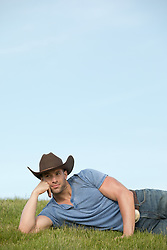 hot cowboy relaxing on a grassy hillside