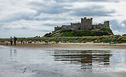 """Bamburgh Castle along North Sea shoreline, Northumberland, England, United Kingdom, Europe. The site of Bamburgh Castle was originally the location of a Celtic Brittonic fort known as Din Guarie, possibly the capital of the kingdom of Bernicia from its foundation circa 420-547. After passing between Britons and Anglo-Saxons three times, Anglo-Saxons gained control in 590, but it was destroyed by Vikings in 993. The Normans later built a new castle here, forming the core of the present one. After a revolt in 1095 (supported by the castle's owner), it became the property of the English monarch. 1600s financial difficulties led to its deterioration. Various owners restored it from the 1700s-1800s, ending with complete restoration by Victorian era industrialist William Armstrong. Today, the owning Armstrong family keeps Bamburgh Castle open to the public. It was a film location for """"Robin Hood"""" (2010) directed by Ridley Scott."""